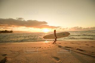 砂浜の上にサーフボードを運ぶ人の写真・画像素材[1129639]