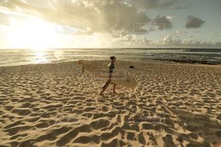 海の横にある砂浜の上を歩く人々 のグループの写真・画像素材[1129855]