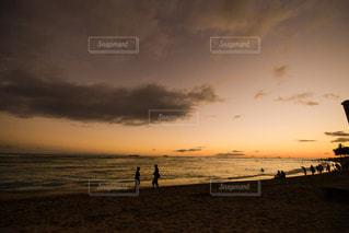 バック グラウンドで夕焼けのビーチに立っている人の写真・画像素材[1136548]