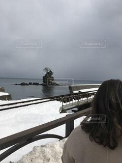 雪の中でベンチに座っている人の写真・画像素材[1138617]