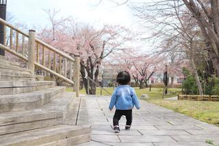 フェンス近くの歩道の上を歩く少年の写真・画像素材[1134781]