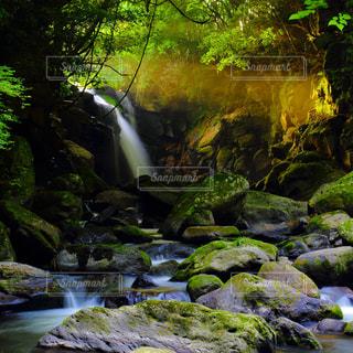 岩の横にある大きな滝の写真・画像素材[1134987]