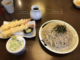 食品やコーヒー テーブルの上のカップのプレートの写真・画像素材[1135441]