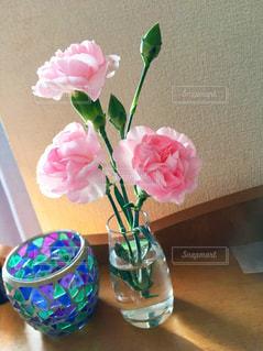 ベッドテーブルの上の花の花瓶とキャンドル - No.1135724