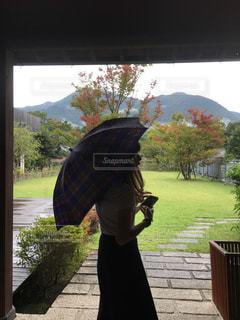 大きな傘の前に立っている人の写真・画像素材[1137958]