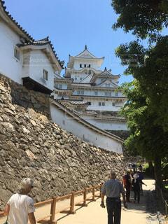 石造りのバック グラウンドで姫路城の建物の前に立っている人々 のグループの写真・画像素材[1156634]