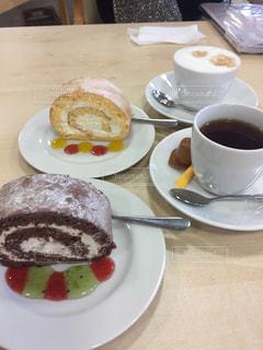 ロールケーキとコーヒーのカップのプレートの写真・画像素材[1140904]