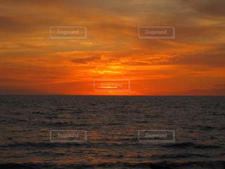 海の横にあるビーチに沈む夕日の写真・画像素材[1144242]