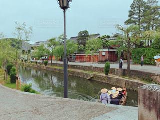 川の近くのベンチに座っている人々 のグループの写真・画像素材[1205278]