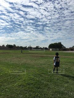 芝生のフィールドに立っているサッカー少年の写真・画像素材[1149773]