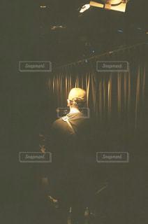 暗い部屋に座っている人の写真・画像素材[2889558]