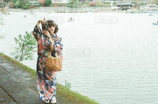 水の体の隣に立っている人の写真・画像素材[3131511]