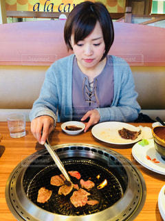 食べ物の皿の前のテーブルに座っている人の写真・画像素材[1274717]
