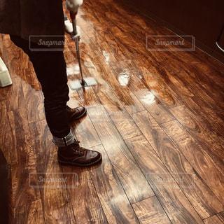 堅い木製の床の側をスケート ボードに乗る人の写真・画像素材[1150086]