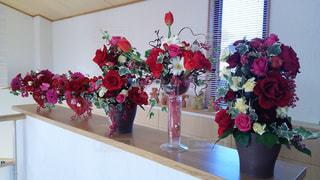 テーブルの上に座っての花で一杯の花瓶の写真・画像素材[1193931]