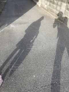 歩道の上に立っている影の写真・画像素材[1187349]