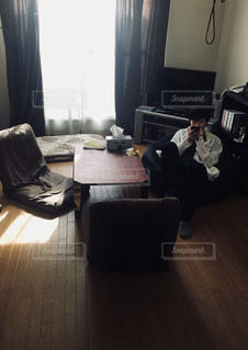 小さな部屋で机に座っている人 - No.1153631