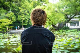 湖の前に立っている男の写真・画像素材[1285752]