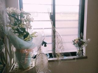 窓の前で花と花瓶の写真・画像素材[1154857]