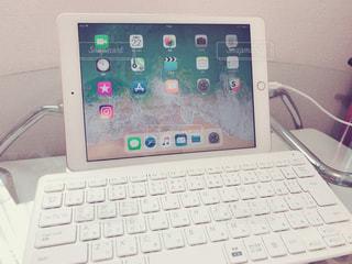 テーブルの上にあるiPad第6世代とBluetoothキーボードの写真・画像素材[1251128]