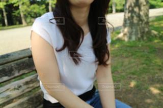 公園のベンチに座っている女性の写真・画像素材[1151974]