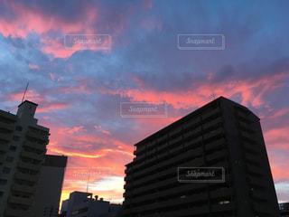 背景の夕日と大きな背の高い建物の写真・画像素材[1152469]