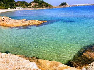 水の体の横にある岩のビーチの写真・画像素材[1617105]
