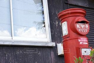 建物の側に座っている赤い消火栓の写真・画像素材[1519543]