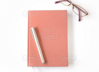 ピンクのノートと眼鏡の写真・画像素材[1553074]