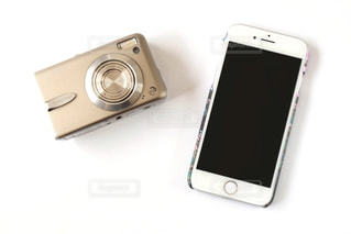 テーブルの上の携帯電話とカメラの写真・画像素材[1553090]