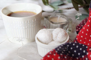 テーブルの上のコーヒーカップと焼き菓子の写真・画像素材[1643249]