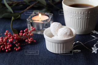 テーブルの上のコーヒーとクッキーとキャンドルの写真・画像素材[1643296]