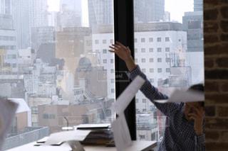 窓の前で俯いている人の写真・画像素材[2086958]