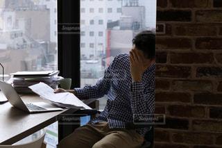 窓の前のテーブルで俯く人の写真・画像素材[2086960]