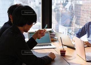 テーブルに座って打ち合わせ中の男性の写真・画像素材[2092607]