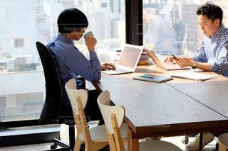 パソコンを使ってテーブルに座っているグループの写真・画像素材[2110892]