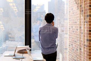 窓の前に立っている男性の写真・画像素材[2110965]