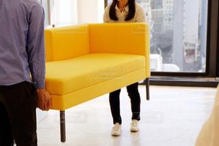 黄色いソファを持つ人の写真・画像素材[2202271]