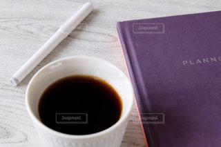 テーブルの上のノートとカップの写真・画像素材[2247595]