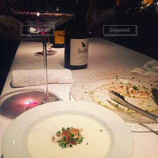食品とテーブルの上にワインのグラスのプレートの写真・画像素材[1160064]