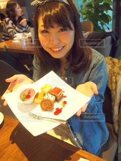 食べ物を食べているテーブルに座っている人の写真・画像素材[2881595]