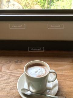 テーブルの上のコーヒー カップと窓の外の写真・画像素材[1462552]