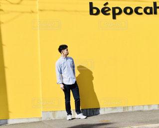 黄色い壁の前に立っている男 - No.1161949