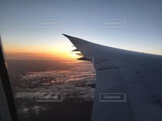 夕暮れの雲の上を飛ぶ飛行機の写真・画像素材[1162142]