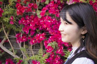 花の前に立っている女性の写真・画像素材[1173044]