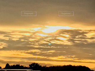 夕焼け空に浮かぶ雲のグループの写真・画像素材[1212828]