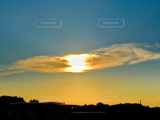 白い雲の中心にオレンジの太陽の写真・画像素材[1365917]