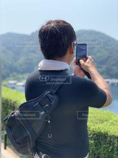 携帯電話で舟屋と海をパチリの写真・画像素材[2373548]