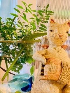 テーブルの上に座っている陶器の猫の写真・画像素材[3717328]