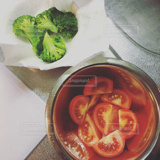 緑のブロッコリーと、ボウルに入った真っ赤なトマトの写真・画像素材[1170004]